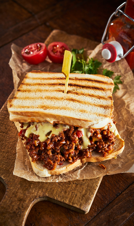 Close up view of tasty sloppy joe sandwich with minced meat and cheese against wooden cutting board