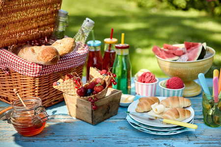 Colorful summertime arrangement of fruit, bread, honey and ice cream on weathered picnic table