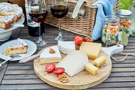 Selection of cheese on a cheeseboard at a picnic on a wooden outdoor table with a wicker hamper, pickles, freshly baled cake for dessert and glasses of red wine