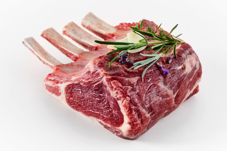 Single raw portion rack of lamb with bone-in chops topped with a sprig of fresh rosemary for seasoning isolated on white Stockfoto