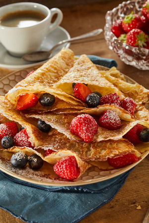 Crispy golden fried crepes filled with assorted fresh ripe berries including strawberries, raspberries and blueberries in a close up view for menu advertising
