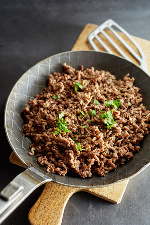 Pan with fried minced meat and chives against wooden cutting board Stockfoto