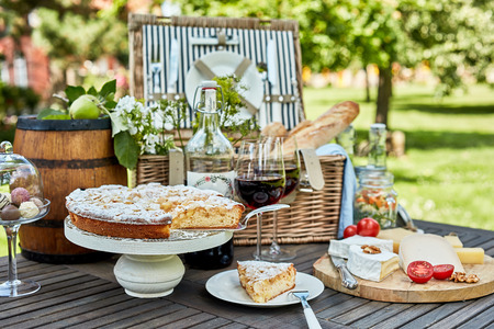 Assorted desserts and cheeses on plates next to picnic basket on rustic wooden table in bright sunlit meadow during summer season