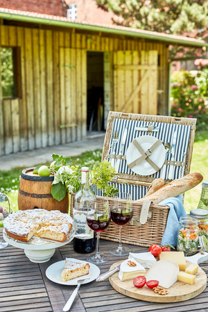 Gourmet picnic hamper served outdoors on a garden table with a selection of cheeses, red wine, pickles, bread and freshly baked tart for dessert