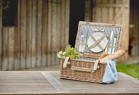 Open fitted wicker picnic hamper with plates, cutlery and French baguettes on a garden table outside a timber cabin with copy space Reklamní fotografie