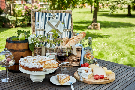 Gourmet picnic lunch under a tree in a park laid out on a wooden slatted table with a hamper, bread, cheese, wine, chocolates and tart for dessert Stock Photo