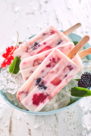 Delicious frozen yogurt and berry popsicles made with fresh red currants and blackberries garnished with mint chilling in a bowl of ice