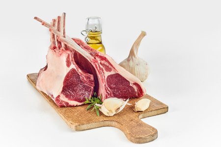 Two uncooked fatty racks of lamb with bone-in chops and fresh ingredients for cooking including clove garlic, herbs and olive oil isolated on white