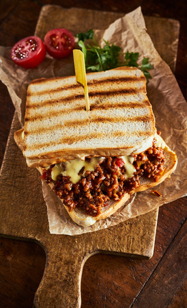 Close up view of sloppy joe sandwich with minced meat against wooden cutting board Stock fotó