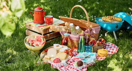 Angled view of picnic blanket and basket next to small blue barbecue and wooden box sitting in green field with dappled sunlight and blurry leaf in foreground