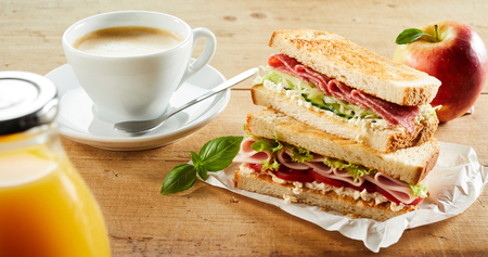 Cup of coffee, apple and double sandwich with ham on table