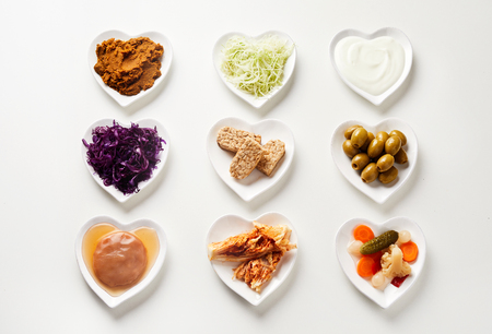 Selection of fermented foods in heart-shaped dishes essential for a healthy gut with a scoby, pickles, vegetables and coconut milk or yogurt