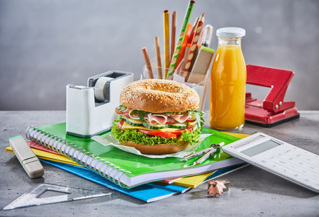 Snacks on schoolwork and surrounded by calculator and tape holder next to container of pencils on granite table with marbled background Stock Photo