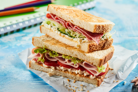 Close up view of tasty fresh sandwiches with ham, cheese and salad