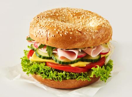 Pan de sésamo crujiente o bagel con relleno de jamón, queso y ensalada en papel sobre blanco para publicidad o un menú Foto de archivo