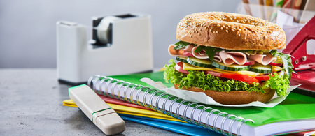 Meat and lettuce sandwich sitting on notebook and folders next to white tape dispenser on top of table Stock Photo