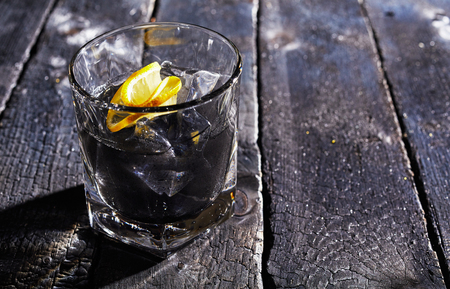 Cocktail with activated charcoal on ice garnished with lemon and served on a rustic wood table with copy space Stock Photo
