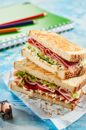 Toasted ham and pastrami sandwiches with salad trimmings for a tasty school lunch served on paper on a blue background with notebook and pencils 스톡 콘텐츠