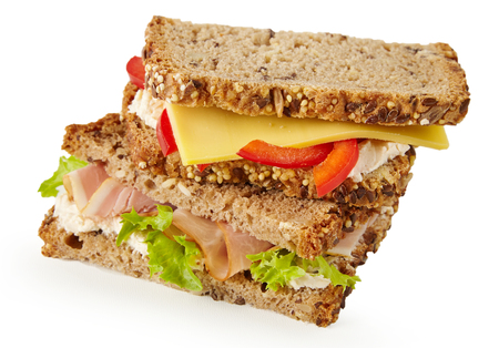 Healthy wholegrain bread sandwiches with ham and lettuce and cheese with tomato stacked on top of one another isolated on white for a tasty lunchtime snack
