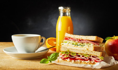 Delicious toasted ham sandwiches, fresh fruit, orange juice and coffee for breakfast on a wooden table or desk wide angle with copy space 版權商用圖片