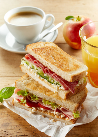 Breakfast set with fresh tasty sandwich, cup of coffee and orange juice