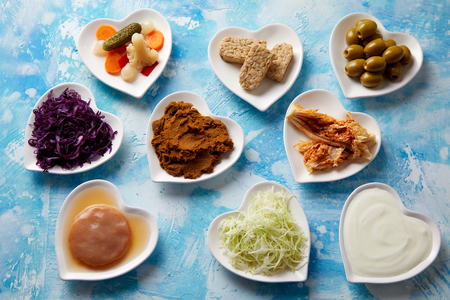 An assortment of fermented foods in heart-shaped dishes viewed from above on a mottled blue background for a healthy diet and gut