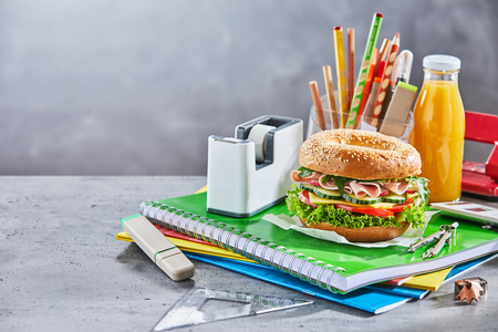 Seeded bagel sandwich on top of notebook and schoolwork next to orange juice and transparent plastic pencil holder on table with smoky background