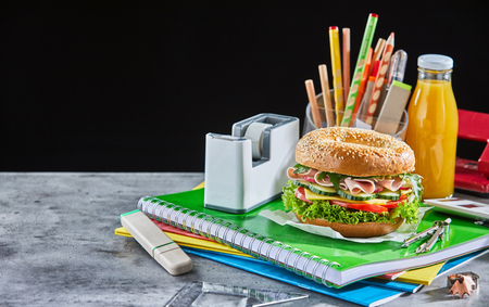 Burger and orange juice bottle on school supplies next to clear pencil holder and white rectangular on marble table with black background tape dispenser Фото со стока