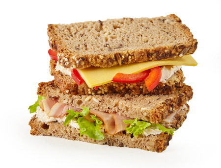 Healthy wholegrain sandwich with ham, lettuce, tomato and cheese isolated o white stacked on top of one another