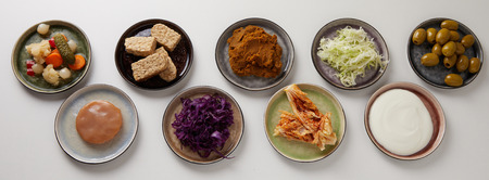 Assorted plates of fermented foods in panorama banner with yogurt, pickles, beet, sauerkraut, scoby, miso, and olives for a healthy gut viewed from above