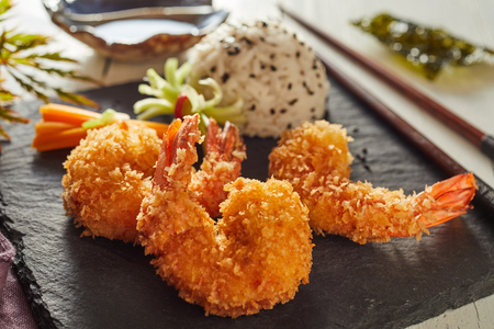 Crispy fried shrimp tails in Japanese tempura batter served with white rice on a black slate board in a restaurant