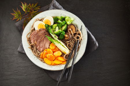 Plate of Gomoku Yakisoba or stewed Japanese pork, black spaghetti noodles and vegetables viewed from above on black slate with copy space