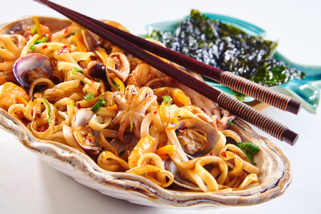 Clamshell filled with cooked rice and seafood. Pair of chopsticks on top and side dish with seaweed. Stock Photo - 107074800