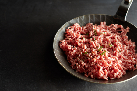 Frying-pan with raw minced meat and chives in close up view
