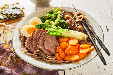 Delicious sliced Japanese stewed pork or Gomoku Yakisoba with vegetables, mushrooms, egg and black spaghetti served on a rustic plate with chopsticks