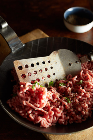 Close up view of minced meat, green chives on pan with spatula