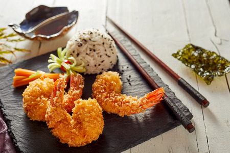 Crispy golden tempura shrimps with rice served on a square slab of black slate for a delicious starter to a Japanese dinner on a rustic white table