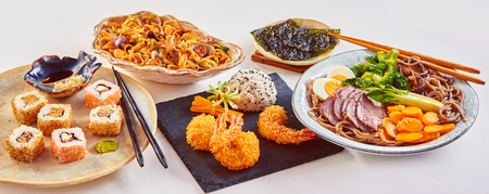 Panorama banner of traditional Japanese dishes with uramaki sushi, gomoku yakisoba, tempura shrimp and fried noodles with shellfish and squid