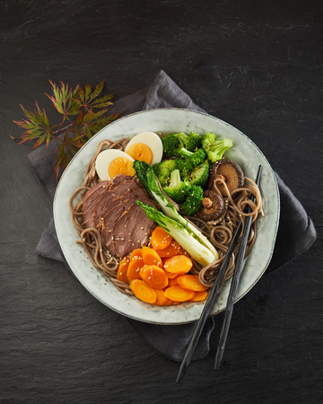 Traditional Japanese stewed pork or Gomoku Yakisoba sliced and served with black noodles, broccoli, carrots, bok choy and egg viewed from overhead with chopsticks on black slate Stock fotó
