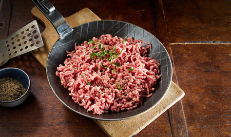 Pan with raw minced meat and chives against wooden cutting board