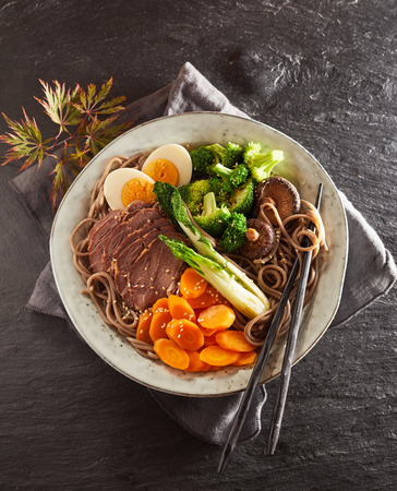 Plate of traditional Japanese stewed pork, or Gomoku Yakisoba, with black spaghetti, mushrooms, egg and vegetables viewed from overhead on slate Stock fotó