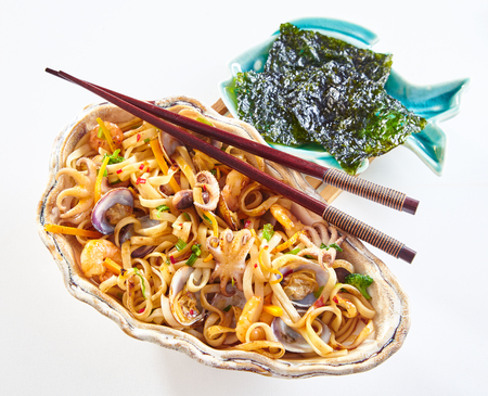 Fried Japanese seafood noodles with squid, calamari, shrimp and shellfish served i a large shell with chopsticks and a side dish of nori over white