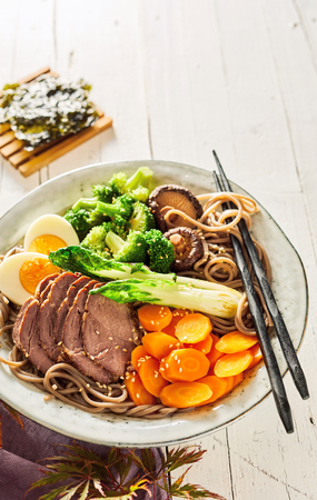 Plate of traditional Japanese Gomoku Yakisoba, or stewed pork, sliced and served with fresh vegetables and black spaghetti on a rustic plate with copy space