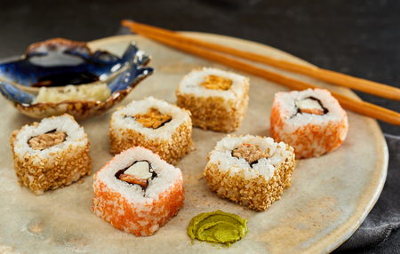 Tasty Uramaki Sushi rolls covered in sesame seeds served with wasabi on a rustic plate in a close up cropped view