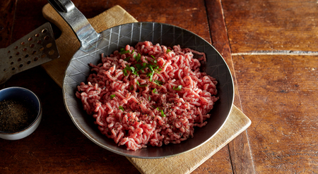 Raw minced meat with chives prepared on pan in kitchen
