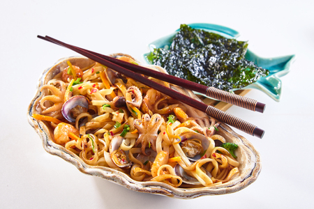 Freshly prepared clamshell dish with noodles and seafood plate and chopsticks over white background