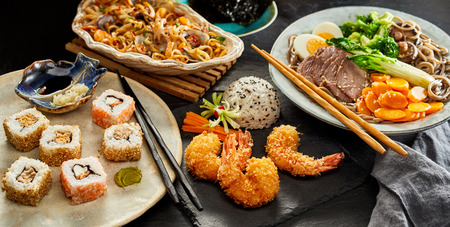 Tables spread with traditional Japanese cuisine including sushi, gomoku yakisoba, fried noodles with assorted seafood and tempura prawns