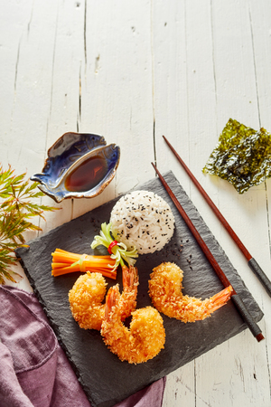 Three fried Japanese tempura shrimp tails in crispy golden batter served with white herb rice on a slab of black slate viewed from above on white wood with copy space Stock Photo