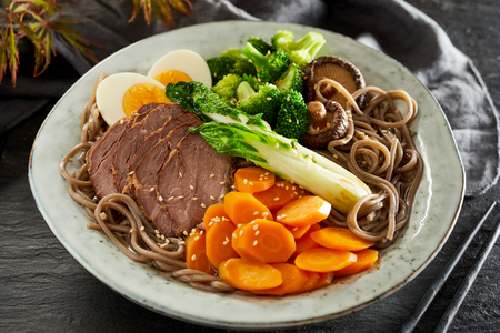 Speciality Japanese Gomoku Yakisoba, or sliced stewed pork, on black spaghetti with fresh vegetables and egg sprinkled with sesame seed Stock fotó