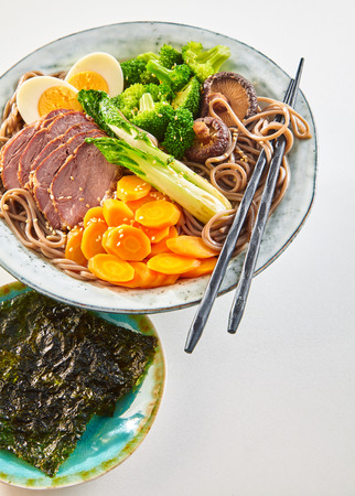 Japanese stewed pork or Gomoku Yakisoba served with roasted noodles, egg and fresh vegetables garnished with sesame and a side dish of nori seaweed on white with copy space